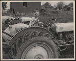 Young Wayne Carlin posing on a Ford tractor, Kosciusko County, Ind., 1949