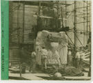 Workers assembling a large limestone carving of an eagle