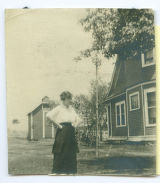 Emma Hoops standing in the side yard of Linger Lodge, 1905.