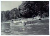 Nancy Blough driving a Starcraft boat past Linger Lodge, 1953