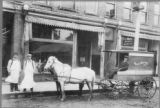 B. Weaver Meat Market & Grocer Delivery Wagon & Star Clothing Store on East Main Street in...