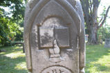 Symbol of Bible in hand on tombstone