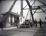 Harmony Way Bridge toll house with Mose Day, the collector, and A. L. Hart, his wife, and daughter...